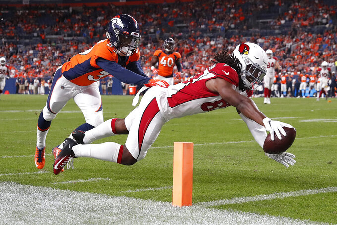 Arizona Cardinals wide receiver A.J. Richardson (83) dives for a touchdown as Denver Broncos cornerback Trey Johnson defends during the second half of an NFL preseason football game, Thursday, Aug. 29, 2019, in Denver. (AP Photo/David Zalubowski)