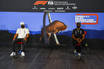 FILE - In this July 2, 2020, file photo, Mercedes drivers Valtteri Bottas of Finland, left and Lewis Hamilton of Britain speak during the drivers news conference the at the Red Bull Ring racetrack in Spielberg, Austria. As sports prepare to resume, journalists are facing the same reckoning that their colleagues who cover politics, education and entertainment have encountered — coming up with new approaches to coverage with reduced access and resources. Professional leagues closed media access to locker rooms and clubhouses in early March.(Mark Sutton/Pool via AP, File)