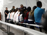 Migrants who are applying for asylum in the United States go through a processing area at a new tent courtroom at the Migration Protection Protocols Immigration Hearing Facility, Tuesday, Sept. 17, 2019, in Laredo, Texas. (AP Photo/Eric Gay)