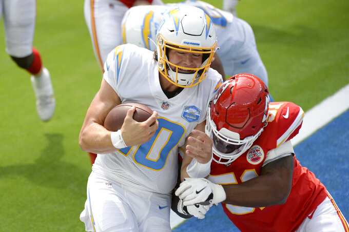 Los Angeles Chargers quarterback Justin Herbert runs into the end zone for a touchdown next to Kansas City Chiefs defensive end Michael Danna during the first half of an NFL football game Sunday, Sept. 20, 2020, in Inglewood, Calif. (AP Photo/Kyusung Gong)