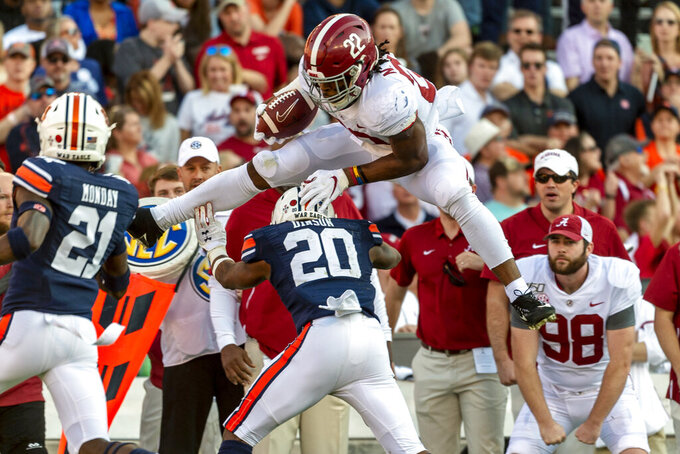 FILE - Alabama running back Najee Harris (22) hurdles Auburn defensive back Jeremiah Dinson (20) during the first half of an NCAA college football game, Saturday, Nov. 30, 2019, in Auburn, Ala. Harris is a candidate for the Doak Walker Award, for outstanding running back. (AP Photo/Vasha Hunt, File)