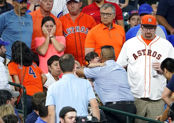 FILE - In this Wednesday, May 29, 2019, file photo, a young child is carried from the stands after being injured by a foul ball off the bat of Chicago Cubs' Albert Almora Jr. during the fourth inning of a baseball game against the Houston Astros, in Houston. Attorney Richard Mithoff on Wednesday, June 26, 2019 provided the first update by the girl's family on her condition since she was hit during the May 29 game. Mithoff says the girl had bleeding and swelling in her brain as well as a brain contusion after she was hit. He says she had a seizure after she was hospitalized and is taking medication to prevent more seizures. (AP Photo/David J. Phillip, File)