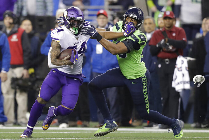 Minnesota Vikings' Irv Smith, left, runs with the ball as Seattle Seahawks' K.J. Wright tries to tackle him during the first half of an NFL football game, Monday, Dec. 2, 2019, in Seattle. (AP Photo/John Froschauer)