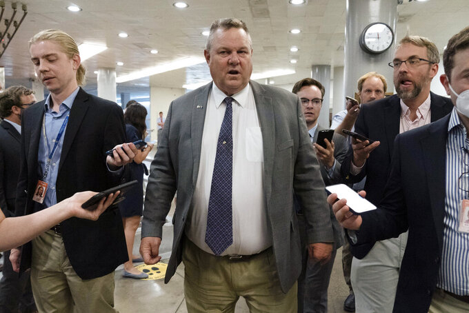 Sen. Jon Tester, D-Mont., talks to reporters as he walks to the Senate chamber ahead of a test vote scheduled by Democratic Leader Chuck Schumer of New York on the bipartisan infrastructure deal senators brokered with President Joe Biden, on Capitol Hill, in Washington, Wednesday, July 21, 2021. Republicans prepared to block the vote by mounting a filibuster over what they see as a rushed and misguided process. (AP Photo/Jose Luis Magana)