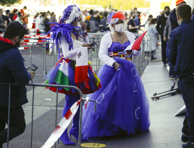 Geert van den Berg, right, queues to attend the show in a purple dress and white wig accessorized with a red feather with his partner Roberto, left, ahead of the first semifinal of the Eurovision Song Contest at Ahoy arena in Rotterdam, Netherlands, Tuesday, May 18, 2021. The competition featuring 39 national songs from nations across Europe as well as Australia and Israel is one of the largest events staged in Europe since the global pandemic began and comes as the continent begins to tentatively ease coronavirus lockdown measures. A crowd of 3,500, tested ahead of time, will be allowed into the Ahoy arena. The number represents a fraction of its capacity to watch the performances live. (AP Photo/Peter Dejong)