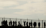 Spectators watch from behind a fence during the first practice session of the Hungarian Formula One Grand Prix at the Hungaroring racetrack in Mogyorod, northeast of Budapest, Hungary, Friday, Aug. 2, 2019. The Hungarian Formula One Grand Prix takes place on Sunday. (AP Photo/Laszlo Balogh)