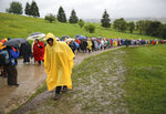 Pilgrims walk during a heavy rainfall to attend Pope Francis' Mass at the Marian shrine, in Sumuleu Ciuc, Romania, Saturday, June 1, 2019. Francis began a three-day pilgrimage to Romania on Friday that in many ways is completing the 1999 trip by St. John Paul II that marked the first-ever papal visit to a majority Orthodox country. (AP Photo/Vadim Ghirda)