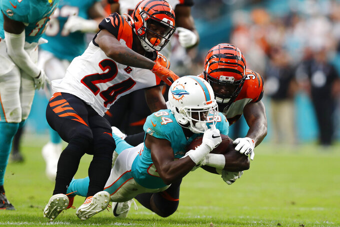 Cincinnati Bengals cornerback Darius Phillips (24) and linebacker Germaine Pratt (57) attempt to stop Miami Dolphins wide receiver Isaiah Ford (84), during overtime at an NFL football game, Sunday, Dec. 22, 2019, in Miami Gardens, Fla. The Dolphins defeated the Begals 38-35. (AP Photo/Brynn Anderson)