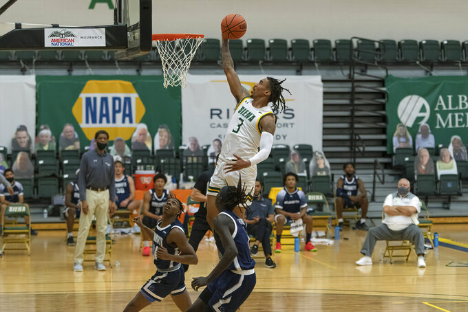 In this photo provided by Siena College, Siena's Manny Camper, top, goes to the basket against Monmouth during an NCAA college basketball game Sunday, Jan. 3, 2021, in Loudonville, N.Y. Siena College finally began its men's basketball season on Sunday against Monmouth, 298 days after its last game. The Saints, the reigning Metro Atlantic Athletic Conference champions, were delayed by three separate pauses due to positive COVID-19 test results from Tier 1 personnel. (Rob Simmons/CSM/Siena College via AP)