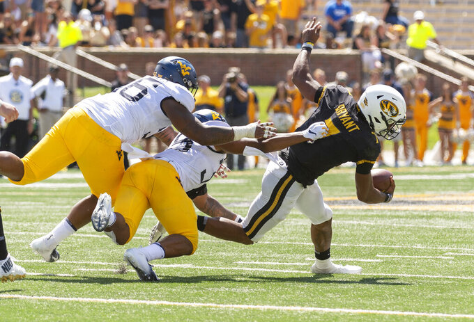 Missouri quarterback Kelly Bryant, right, slips away from West Virginia's Adam Stilley, left, and Josh Chandler, center, as he scrambles during the first half of an NCAA college football game Saturday, Sept. 7, 2019, in Columbia, Mo. Missouri won the game 38-7. (AP Photo/L.G. Patterson)
