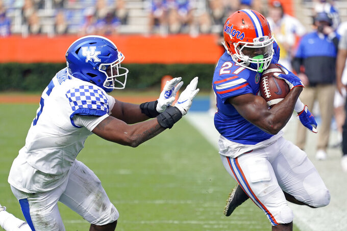 Florida running back Dameon Pierce (27) makes a move to get past Kentucky linebacker DeAndre Square during the second half of an NCAA college football game, Saturday, Nov. 28, 2020, in Gainesville, Fla. (AP Photo/John Raoux)