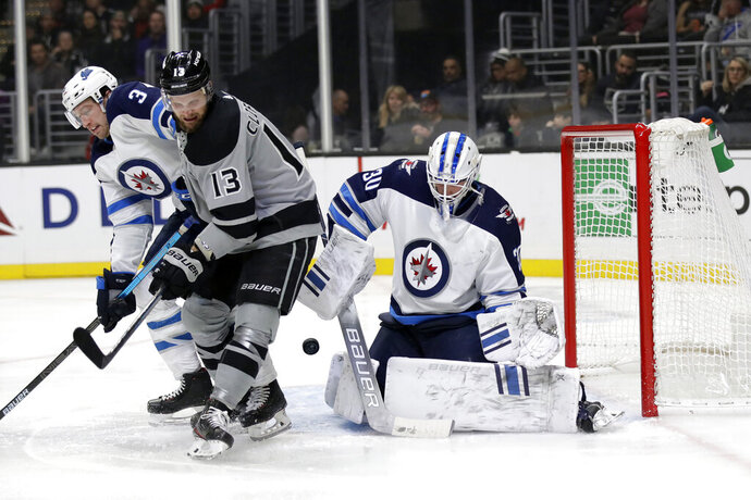 The puck bounces in front of the goal between Winnipeg Jets' Tucker Poolman, left, Los Angeles Kings' Kyle Clifford (13) and Jets goaltender Laurent Brossoit during the second period of an NHL hockey game Saturday, Nov. 30, 2019, in Los Angeles. (AP Photo/Marcio Jose Sanchez)