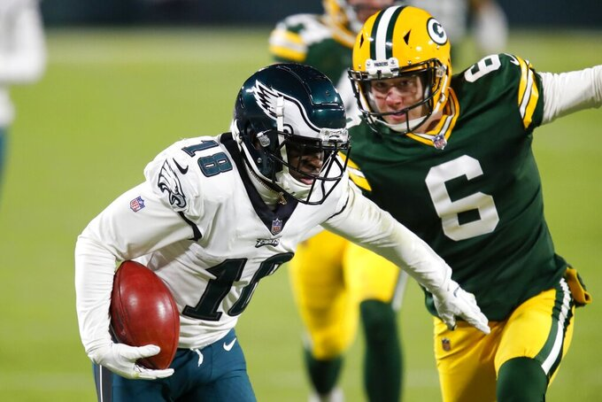 Philadelphia Eagles' Jalen Reagor gets past Green Bay Packers punter J.K. Scott for a touchdown on a punt return during the second half of an NFL football game Sunday, Dec. 6, 2020, in Green Bay, Wis. (AP Photo/Matt Ludtke)