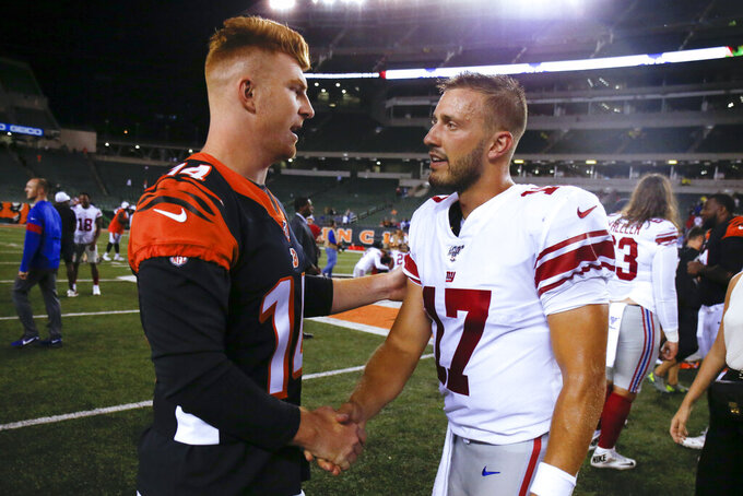 Cincinnati Bengals quarterback Andy Dalton (14) and New York Giants quarterback Kyle Lauletta (17) meet after an NFL preseason football game Thursday, Aug. 22, 2019, in Cincinnati. (AP Photo/Gary Landers)
