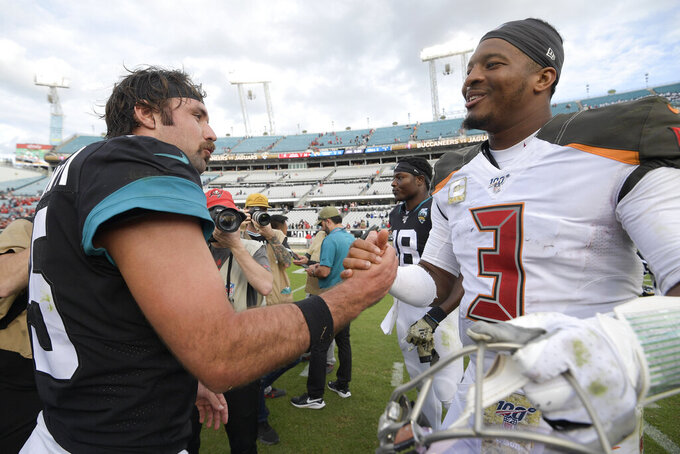 Jacksonville Jaguars quarterback Gardner Minshew, left, and Tampa Bay Buccaneers quarterback Jameis Winston (3) greet each other after an NFL football game, Sunday, Dec. 1, 2019, in Jacksonville, Fla. (AP Photo/Phelan M. Ebenhack)