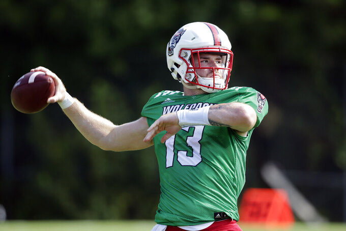 This photo taken Tuesday, Aug. 6, 2019, shows North Carolina State quarterback Devin Leary (13) during an NCAA college football practice in Raleigh, N.C. (AP Photo/Gerry Broome)