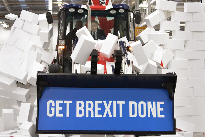 Britain's Prime Minister Boris Johnson sits in the cab to break through a symbolic wall with the Conservative Party slogan 'Get Brexit Done', during an election campaign event at the JCB manufacturing facility in Uttoxeter, England, Tuesday Dec. 10, 2019.  The Conservative Party are campaigning for their Brexit split with Europe ahead of the UK's General Election on Dec. 12. (Stefan Rousseau/PA via AP)