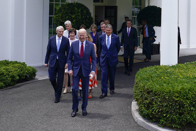 President Joe Biden, with a bipartisan group of senators, walks to speak Thursday June 24, 2021, outside the White House in Washington. Biden invited members of the group of 21 Republican and Democratic senators to discuss the infrastructure plan. For a president who had campaigned on his ability to work across the aisle, Joe Biden's announcement of a bipartisan deal on a $1.2 trillion infrastructure package was a victory. He was flanked Thursday by Democrats and Republicans alike, who dutifully spoke about the virtues of consensus. (AP Photo/Evan Vucci)