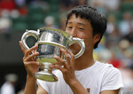 Japan's Shintaro Mochizuki kisses the trophy after defeating Spain's Carlos Gimeno Valero during the boys' singles final match of the Wimbledon Tennis Championships in London, Sunday, July 14, 2019. (AP Photo/Kirsty Wigglesworth)