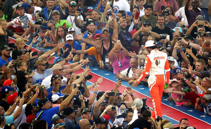 FILE - Fans reach out to high-five pole-sitter Chase Elliott during driver introductions for the NASCAR Sprint Cup auto race at Daytona International Speedway, Saturday, July 7, 2018, in Daytona Beach, Fla. NASCAR has built itself around its traveling show, every weekend a super-charged event of concerts, camping and infield carousing that closes with a Cup race. The party has been canceled during the pandemic but the playoffs go on, starting Sunday, Sept. 6, 2020, without any of the pomp and circumstance. (AP Photo/John Raoux, File)