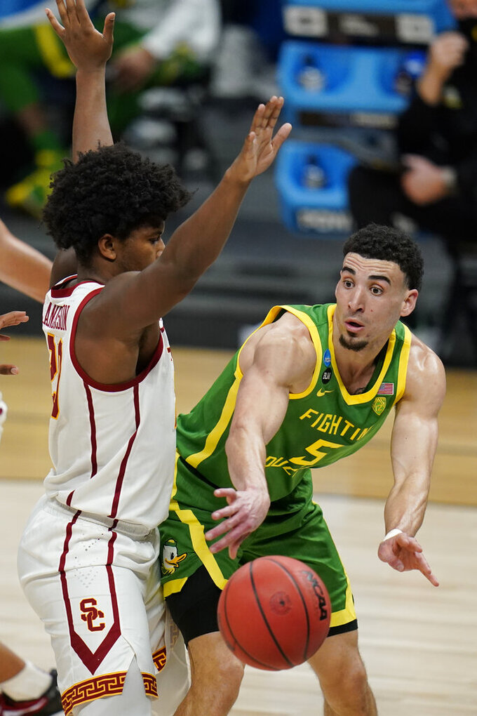 Oregon guard Chris Duarte (5) passes around Southern California guard Ethan Anderson, left, during the second half of a Sweet 16 game in the NCAA men's college basketball tournament at Bankers Life Fieldhouse, Sunday, March 28, 2021, in Indianapolis. (AP Photo/Jeff Roberson)