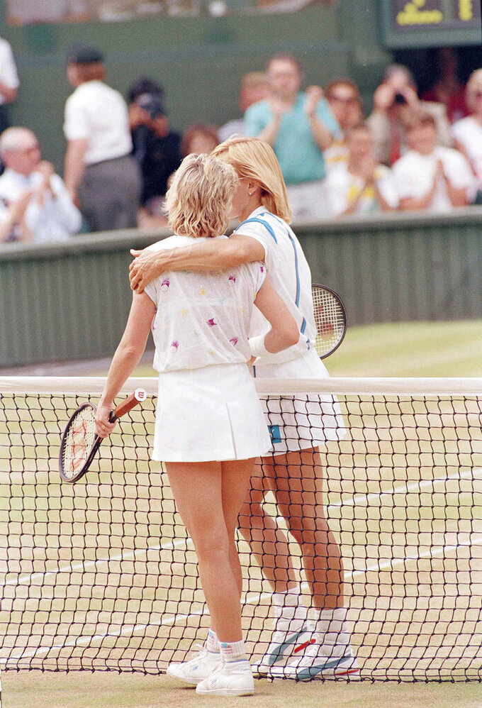 FILE - In this July 2, 1987, file photo, Chris Evert, left, is consoled by defending champion Martina Navratilova as they leave Wimbledon's Centre Court at the end of their women's singles semifinal match. Navratilova won the match 6-2, 5-7, 6-4. (AP Photo/Adam Stoltman, FIle)