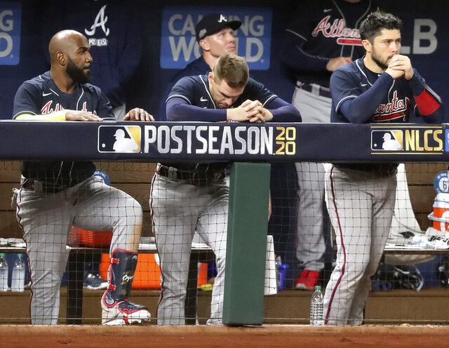 Atlanta Braves' Ozzie Marcell Ozuna, Freddie Freeman and Travis d'Arnaud react in the dugout after falling 4-3 to the Los Angeles Dodgers in Game 7 of a baseball National League Championship Series, Sunday, Oct. 18, 2020, in Arlington, Texas. (Curtis Compton/Atlanta Journal-Constitution via AP)