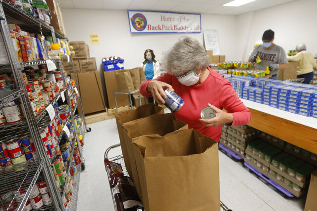 Hands Across Middlesex Food Pantry volunteer, Mary Ellen Sherwood, pack bags of food for their food pantry distribution Monday April 27, 2020, in Locust Hill, Va. The rural food pantry has seen its membership spike in the weeks since the coronavirus pandemic has walloped the economy. (AP Photo/Steve Helber)