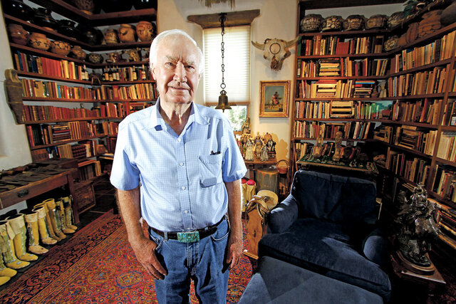 FILE - In this July 4, 2014 file photo, Forrest Fenn poses at his Santa Fe, N.M., home. The antiquities dealer and author who gained fame after hiding a treasure in the Rocky Mountains has died at the age of 90. Police confirmed Fenn died Monday, Sept. 7, 2020, of natural causes at his home in Santa Fe. (Luis Sanchez Saturno/Santa Fe New Mexican via AP, File)