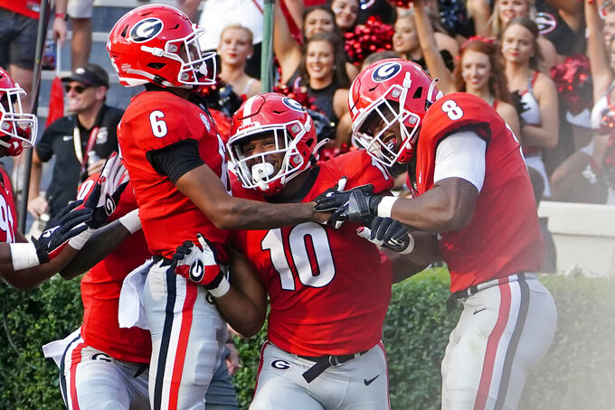 Georgia linebacker Jamon Dumas-Johnson (10) celebrates with defensive back Jalen Kimber (6) and linebacker MJ Sherman (8) after returning an interception for a touchdown during the second half of an NCAA college football game against UAB, Saturday, Sept. 11, 2021, in Athens, Ga. (AP Photo/John Bazemore)