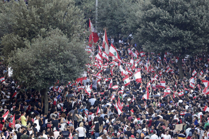 Anti-government protesters shout slogans against the Lebanese government during a protest in Beirut, Lebanon, Saturday, Oct. 19, 2019. The blaze of protests was unleashed a day earlier when the government announced a slate of new proposed taxes, including a $6 monthly fee for using Whatsapp voice calls. The measures set a spark to long-smoldering anger against top leaders from the president and prime minister to the numerous factional figures many blame for decades of corruption and mismanagement. (AP Photo/Hassan Ammar)