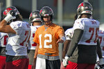 Tampa Bay Buccaneers quarterback Tom Brady (12) fist bumps offensive tackle Donovan Smith (76) as they line up for a play during an NFL football practice Tuesday, July 27, 2021, in Tampa, Fla. (AP Photo/Chris O'Meara)