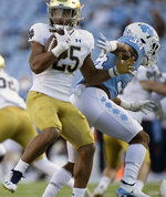 Notre Dame's Chris Tyree (25) spins away from North Carolina's British Brooks (34) in the second quarter of an NCAA college football game, Friday, Nov. 27, 2020, at Kenan Stadium in Chapel Hill, N.C. (Robert Willett/The News & Observer via AP)