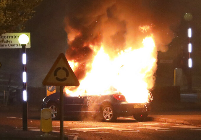A car burns after it was hijacked by Loyalists at the Cloughfern roundabout in Newtownabbey, Belfast, Northern Ireland, Saturday, April 3, 2021. Masked men threw petrol bombs and hijacked cars in the Loyalist area North of Belfast. Loyalists and unionists are angry about post-Brexit trading arrangements which they claim have created barriers between Northern Ireland and the rest of the UK. (Peter Morrison/PA via AP)