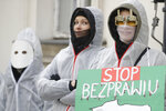 """FILE - In this Saturday, Dec. 19, 2020 file photo, participants with a sign reading """"Stop Lawlessness"""" and wearing anti-COVID-19 overalls take part in a protest against new pandemic restrictions and planned lockdown during the holiday season before the Health Ministry in Warsaw, Poland.  The coronavirus pandemic has upended life around the globe, but it has hasn't stopped the spread of authoritarianism and extremism. Some researchers believe it may even have accelerated it, but curbing individual freedoms and boosting the reach of the state. Since COVID-19 hit, Hungary has banned children from being told about homosexuality. China shut Hong Kong's last pro-democracy newspaper. Brazil's president has extolled dictatorship. Belarus has hijacked a passenger plane. A Cambodian human rights lawyer calls the pandemic """"a dictator's dream opportunity."""" But there are also resistance movements, as protesters from Hungary to Brazil take to the streets to defend democracy. (AP Photo/Czarek Sokolowski, File)"""