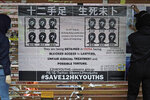 FILE - In this Sept. 29, 2020, file photo, university students put up posters to demand of releasing the 12 Hong Kong activists detained at sea by Chinese authorities, at