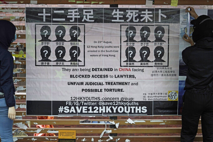 """FILE - In this Sept. 29, 2020, file photo, university students put up posters to demand of releasing the 12 Hong Kong activists detained at sea by Chinese authorities, at """"Lennon Wall"""" in the University of Hong Kong. Lu Siwei, who represented one of 12 Hong Kong activists who tried to flee to Taiwan, had his license revoked by the Sichuan Provincial Justice Department in a formal notice given Friday, Jan. 15, 2021. (AP Photo/Kin Cheung, File)"""