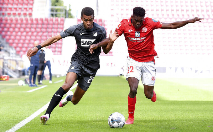 Hoffenheim's Kevin Akpoguma, left, in action with Mainz's Taiwo Awoniyi during the German Bundesliga soccer match between Mainz and Hoffenheim at the Opel Arena stadium in Mainz, Germany, Saturday, May 30, 2020. Because of the coronavirus outbreak all soccer matches of the German Bundesliga take place without spectators. (Sascha Steinbach/pool photo via AP)