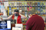 A clerk adjusts his protective mask while waiting on a masked customer at Ted's Stateline Mobil on Wednesday, June 24, 2020 in Methuen, Mass. The coronavirus pandemic has been a rollercoaster for state lotteries across the country, with some getting a boost from the economic downturn and others scrambling to make up for revenue shortfalls. (AP Photo/Charles Krupa)