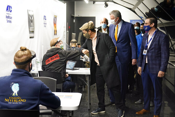 FILE -- In this April 12, 2021 file photo, actor Lin-Manuel Miranda, center, bumps elbows with a worker at the ATC Vaccination Services site in New York's Times Square. He's accompanied by New York Mayor Bill de Blasio, second from right, and ATC Alert founder & CEO Jordan Savitsky, right. Nearly 900 people received expired Pfizer COVID-19 vaccine doses at the vaccination site in Times Square this month, health officials said Tuesday, June 15, 2021. (AP Photo/Richard Drew, Pool, File)