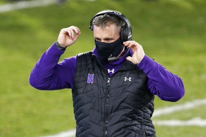 "FILE - Northwestern coach Pat Fitzgerald walks on the field during the fourth quarter of the team's NCAA college football game against Michigan State in East Lansing, Mich., in this Saturday, Nov. 28, 2020, file photo. Pat Fitzgerald figures he'll add a few more gray hairs by the time No. 15 Northwestern steps on the field to face No. 3 Ohio State in the Big Ten championship game on Saturday, Dec. 19. Then again, if Northwestern wins? ""Not gonna lie to you, it would be a helluva ride home on I-65,"" Fitzgerald said.  (AP Photo/Al Goldis, File)"