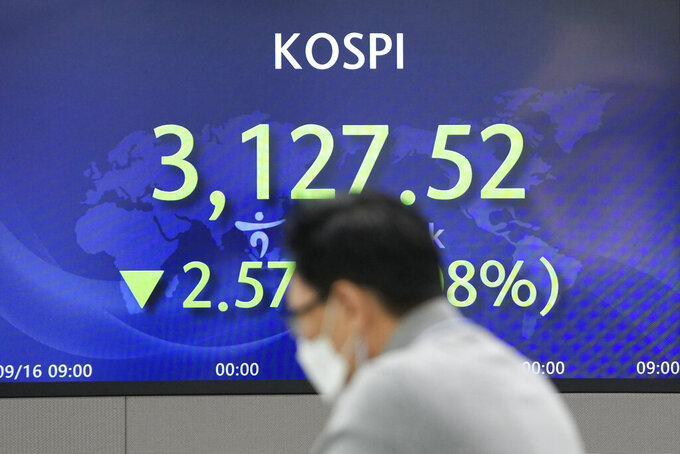 A currency trader talks near the screen showing the Korea Composite Stock Price Index (KOSPI) at a foreign exchange dealing room in Seoul, South Korea, Friday, Sept. 17, 2021. Asian shares were mixed on Friday after a hodge-podge of economic data led Wall Street to close mostly lower. (AP Photo/Lee Jin-man)