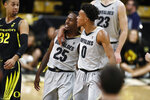 Colorado guard Shane Gatling, right, hugs guard McKinley Wright IV as Oregon guard Anthony Mathis looks on as the teams headinto a time out in the second half of an NCAA college basketball game Thursday, Jan. 2, 2020, in Boulder, Colo. Colorado won 74-65. (AP Photo/David Zalubowski)