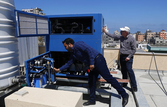 In this Thursday, April 30, 2020 photo, Palestinian engineer Raed Nakhal from Palestine Children Relief Fund, right, and engineer Abdullah Dewik, check the GEN-M machine that generates safe drinking water from air at the roof of al-Rantisi pediatric hospital in Gaza City. A Georgian-Israeli billionaire believes he has found a solution to the Gaza Strip's chronic water crisis. Michael Mirilashvili wants to deliver hundreds of generators that produce drinking water out of thin air. His company, Watergen, has already delivered two of the machines to Gaza in a rare case of Israeli-Palestinian cooperation in the Hamas-ruled enclave. (AP Photo/Adel Hana)