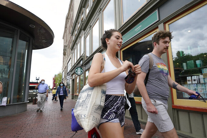 Pedestrians, some wearing masks out of concern for the coronavirus, left, while others, right, go without masks, while walking in the Harvard Square neighborhood, of Cambridge, Mass., Sunday, May 23, 2021. Massachusetts officials say the number of people fully vaccinated against coronavirus in the state is approaching 50%. (AP Photo/Steven Senne)