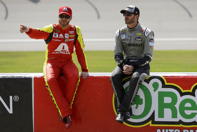 "FILE - In this June 10, 2016, file photo, drivers Dale Earnhardt Jr., left, and Jimmie Johnson talk before qualifying for the NASCAR Sprint Cup series auto race at Michigan International Speedway in Brooklyn, Mich. The mind-boggling success of virtual racing has put motorsports out front in the race to create competition during the sports shutdown caused by the coronavirus pandemic. ""All of the race teams are trying everything they can to keep their sponsors and keep their employees,"" said longtime virtual racing fanatic Dale Earnhardt Jr. (AP Photo/Carlos Osorio, File)"