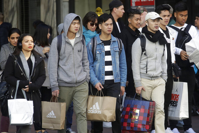 FILE - In this Nov. 29, 2019 file photo, shoppers carry bags as they cross a street in San Francisco. More people turned to online shopping during one of the shortest holiday shopping seasons in years, helping boost total sales. Retail sales in the U.S. rose 3.4% between Nov. 1 and Dec. 24 from a year ago, according to early data from Mastercard SpendingPulse. That's down from last year, when total sales grew 5.1%. Online sales rose at a faster pace, up 18.8% from last year.  (AP Photo/Jeff Chiu)