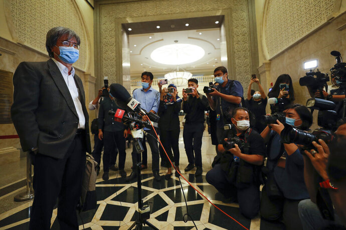 In this picture taken Thursday, July 2, 2020, show Steven Gan, left, editor-in-chief of Malaysiakini online news portal arrive at court in Putrajaya, Malaysia, Monday, July 13, 2020. Attorney General Idrus Harun, who was appointed by a new government that took power in March, filed contempt proceedings against Malaysiakini and Gan over comments made by five readers on its portal last month that allegedly tarnished the judiciary. (AP Photo/Vincent Thian)