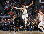 Brooklyn Nets guard Kyrie Irving, front, passes the ball past Denver Nuggets guard Jamal Murray during the first half of an NBA basketball game Thursday, Nov. 14, 2019, in Denver. (AP Photo/David Zalubowski)