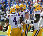 LSU players, including tight end Foster Moreau (18) and offensive tackle Saahdiq Charles (77) celebrate with running back Nick Brossette (4) after he scored a touchdown against Florida on a 4-yard run durinng the first half of an NCAA college football game, Saturday, Oct. 6, 2018, in Gainesville, Fla. (AP Photo/John Raoux)